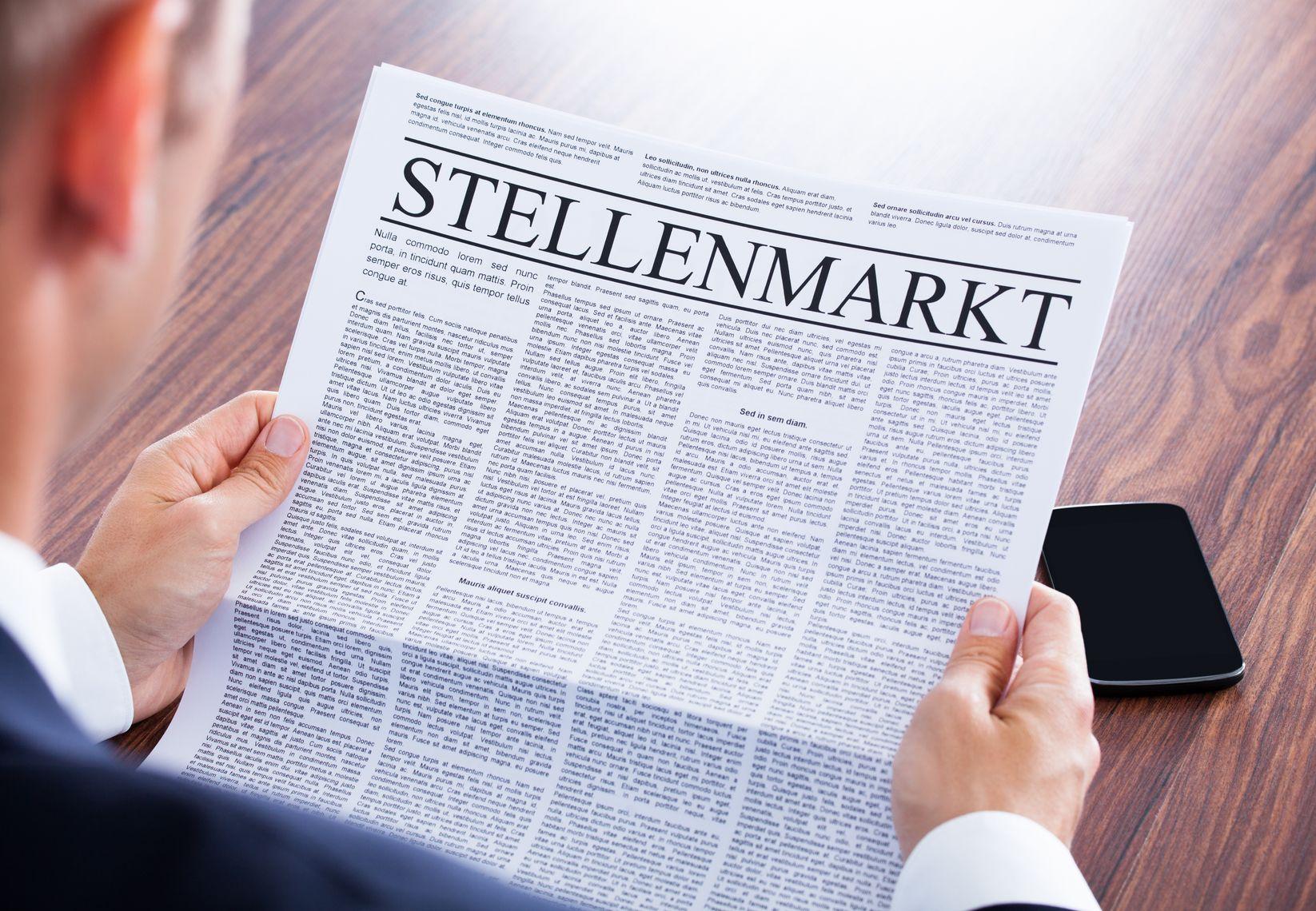 Mann schaut Zeitung mit Stellenmarkt an